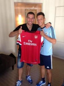Özil sujeta la camiseta del Arsenal con su nuevo compañero, Lukas Podolsky.