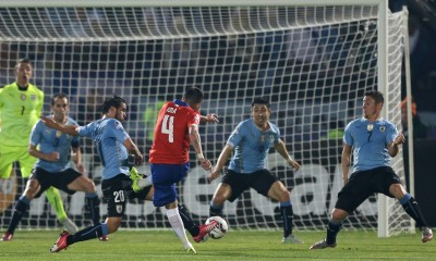 Chile's Mauricio Isla , center, shoots to score the opening goal during a Copa America quarterfinal soccer match against Uruguay at the National Stadium in Santiago, Chile, Wednesday, June 24, 2015. (AP Photo/Ricardo Mazalan)